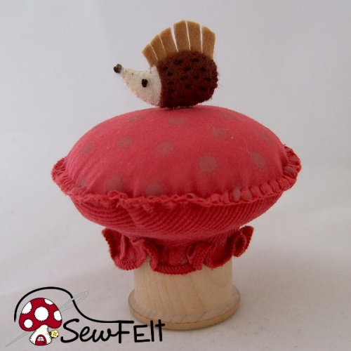 Handmade pincushion with a hedgehog pin and toadstool design