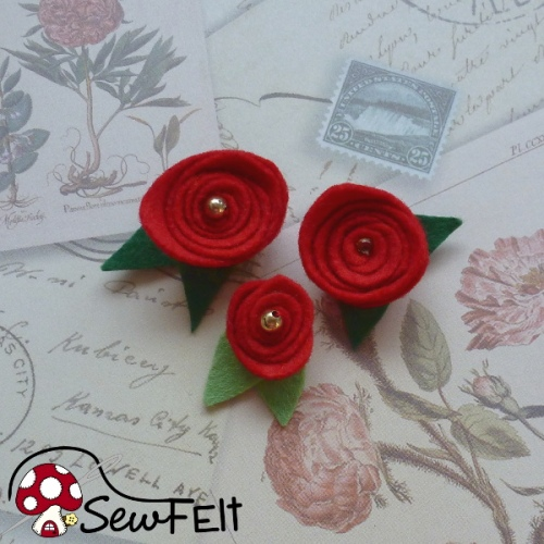 Tiny red felt roses with beads and green leaves on floral paper background