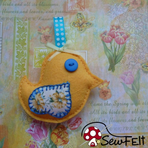Bright yellow felt bird Spring Easter chick design with blue accents on a floral background